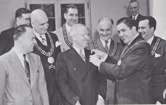 1946 WHITE HOUSE VISIT - The Ahepa Supreme Lodge visits President Harry S. Truman at the White House and officially inducts the President into the Order of Ahepa on March 25, 1946. With President Truman are: Nicholas Economou, Leo J. Lamberson, Frank E. Pofanti, George A. Cotsakis, C. G. Paris, Harris J. Booras, Stephen S. Scopas. ln the background, Michael Loris of New York City, named 'America's No. 1 War Bond Salesman' by the U. S. Treasury Department.