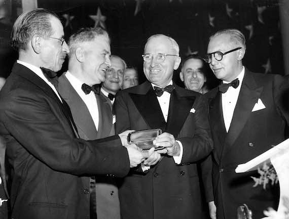 1948 - President Harry S. Truman (second from right) receives an Ahepa gold life membership card at the Ahepa National Banquet in Washington, D. C. from members of the Order of Ahepa, the American Hellenic Educational Progressive Association. From left to right are: Chris G. Garrison, Secretary of the Kansas City AHEPA chapter #73; Thomas Kapsemalis, President of the Kansas City chapter; President Truman; and Dean Alfange